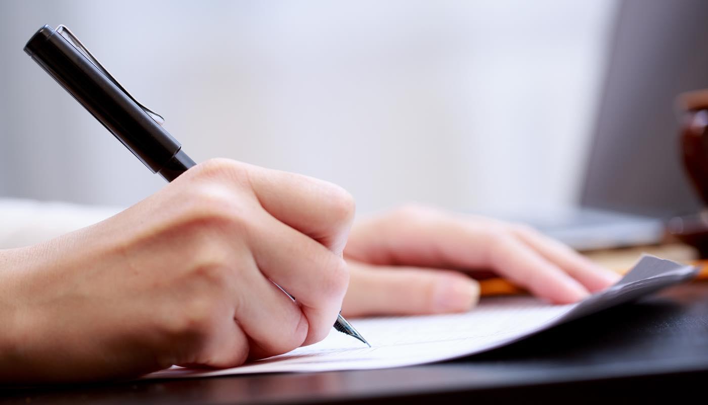 謝罪文を書く女性の手