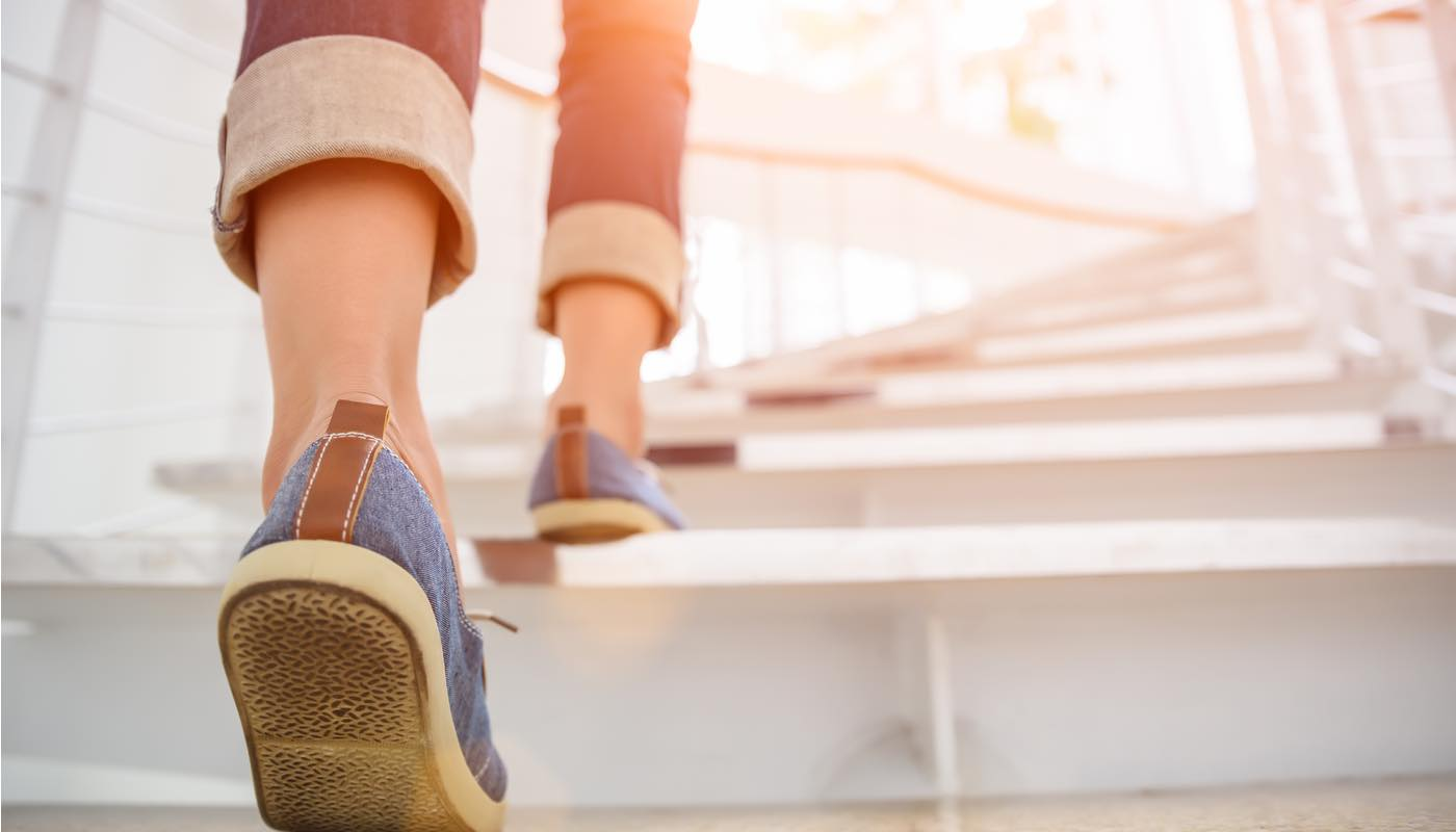 明るい未来に向かって一歩ずつ階段を踏みしめて進む女性