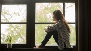 窓辺で体育座りをして彼からの連絡を待つ女性