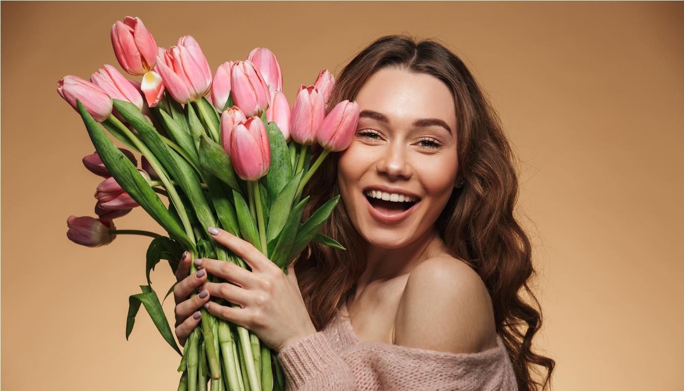 たくさんの花を手にした女性
