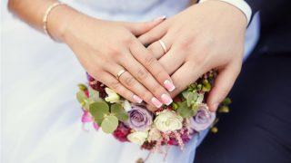 結婚式中に手を重ね合わせる新郎新婦